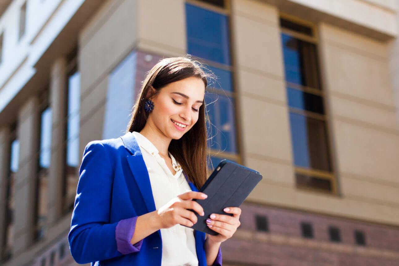 Girl in blue blazer checks her tablet standing on the street