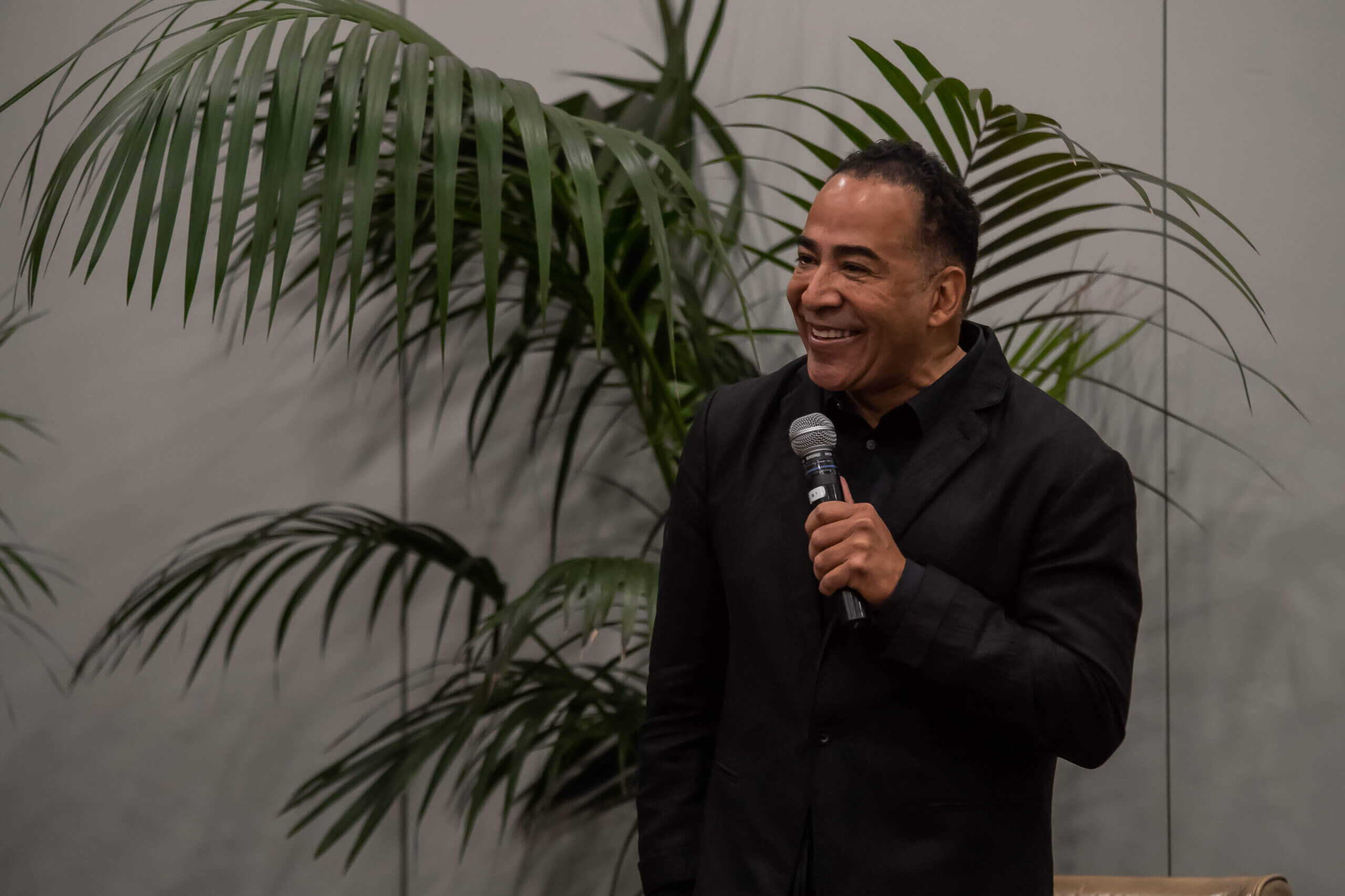 Tim storey smiling and holding a microphone