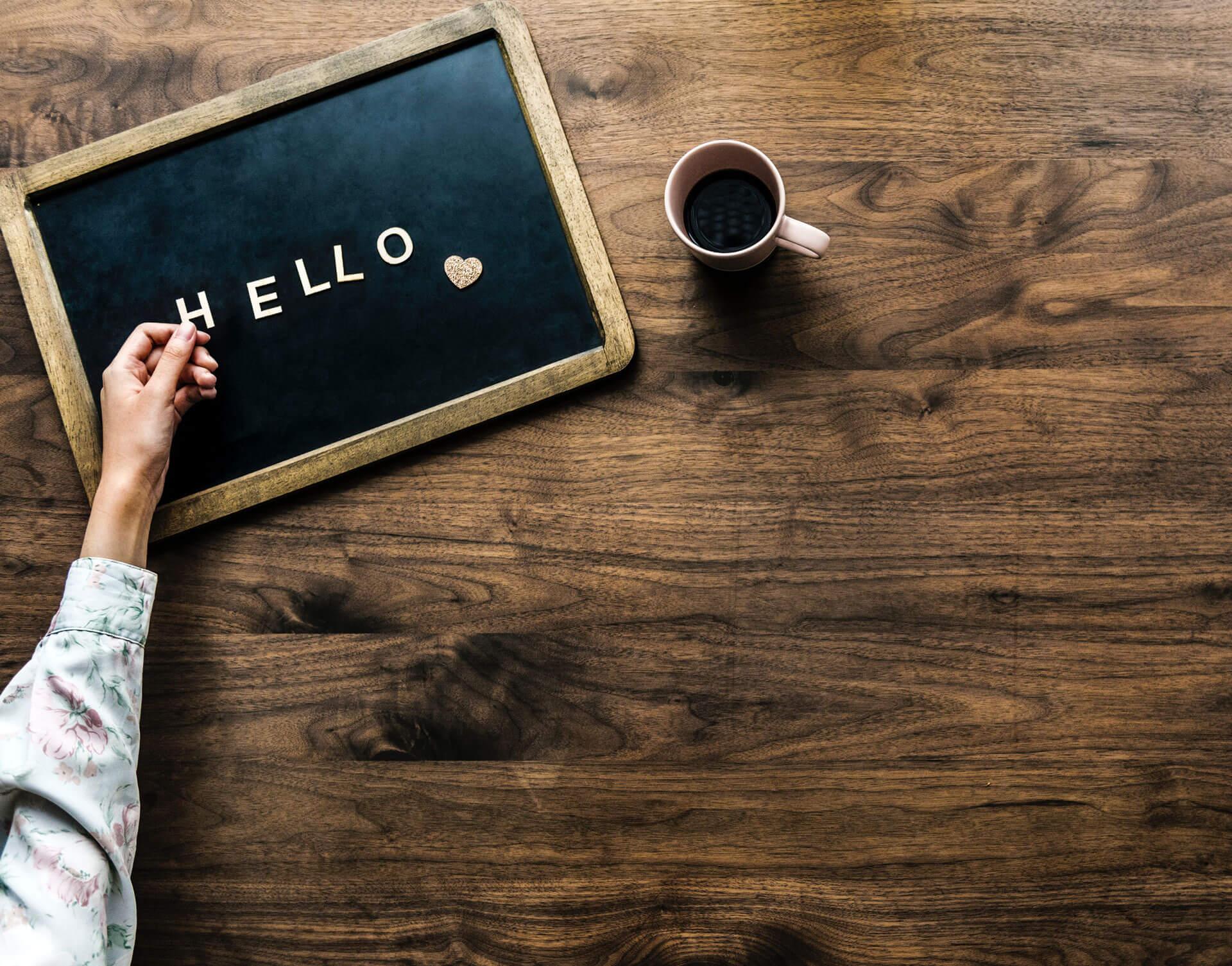 En kaffe kopp och hello på en blackboard