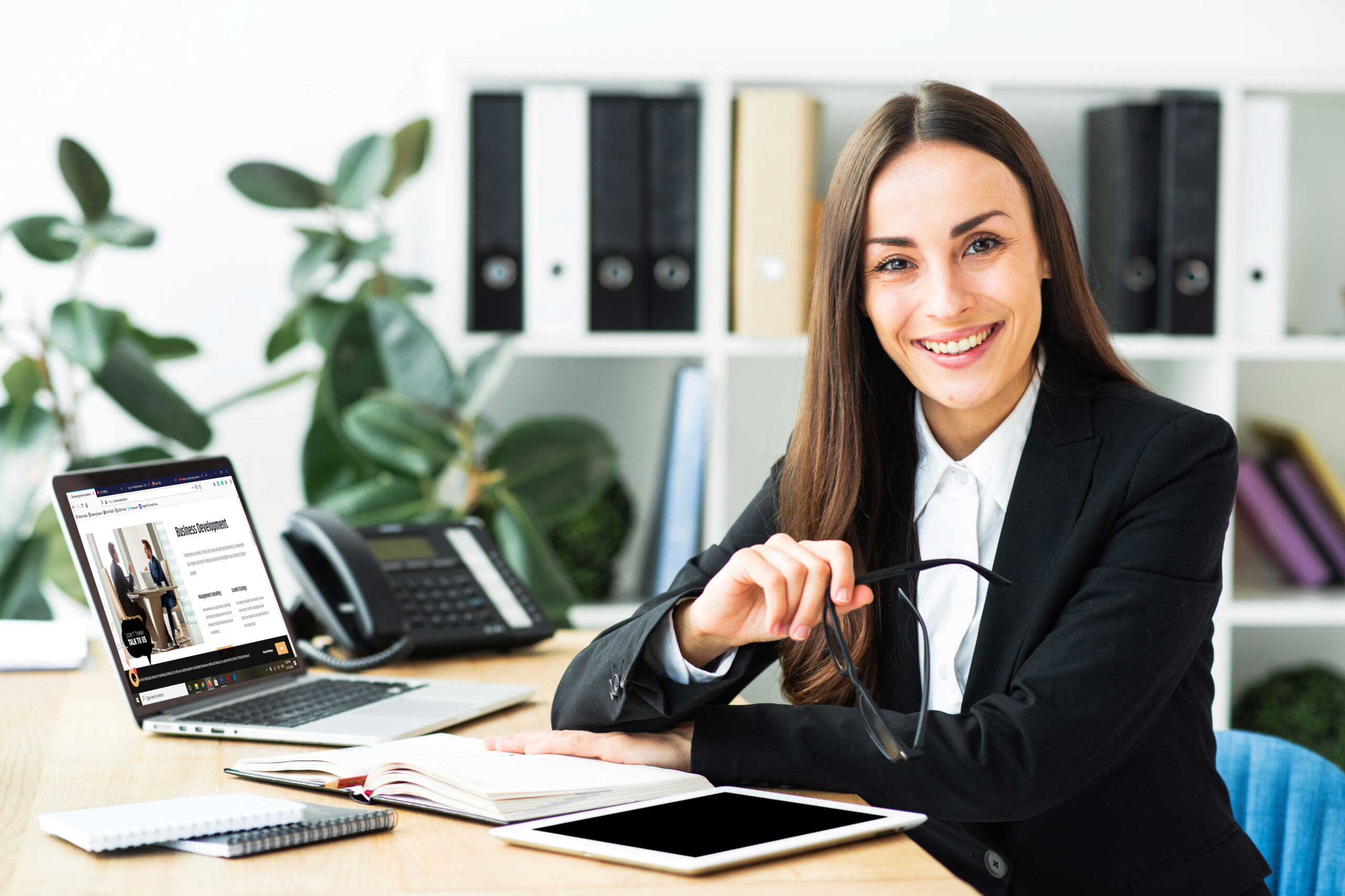 Woman at work, sitting on desk.